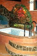 Красная подсветка интерьерного фонтана с водой, сбегающей по каменистым уступам, гармонирует с цветом стен.