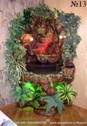 Комнатный водопад на подставке в форме грота. Встроенное галогеновое освещение подсвечивает водяной поток и декоративные растения.