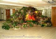 Пример оформления холла крупной композицией из скал, стекающего по ним водопада и растений.