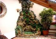 Зимний сад в мансардном этаже загородного дома оформлен с использованием декоративного водопада.