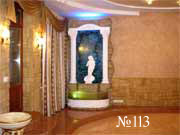Водопад с колоннами и скульптурой соответствует общему стилю интерьера загородного дома.