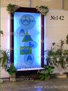 Символика на стекле пристенной водной панели придает неповторимость и индивидуальность холлу одного из деловых зданий. Мрамор в нише и оригинальная отделка камнем и искусственными растениями оживляют интерьер.