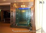 Перед облицованной плиткой нишей с зеркалом размещена прозрачная панель из органического стекла, по которой стекает вода.