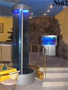 Эта декоративная колонна представляет собой водную панель в форме линзы из оргстекла с подсветкой.