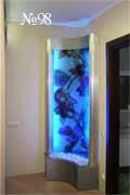 Вогнутая водная панель вписана в угол комнаты. Экзотический рисунок фона и цветная люминесцентная подсветка привлекают взгляд.